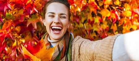 쾌활 한 젊은 여자의 초상화 leafs 단풍 만들기 selfie 만들기의 앞에 스톡 콘텐츠