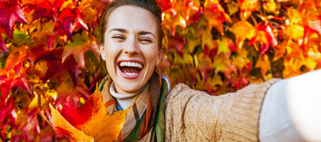 Portrait of cheerful young woman with autumn leafs in front of foliage making selfie Stock Photo