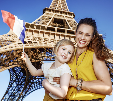 Touristy, without doubt, but yet so fun. Portrait of smiling mother and daughter travellers showing flag against Eiffel tower in Paris, France
