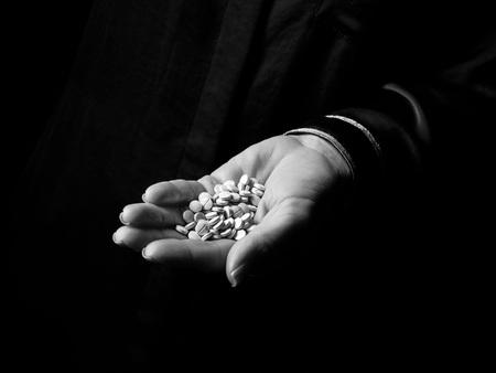 Black Mania. vrouwelijke hand geïsoleerd op zwart weergegeven: blauwe pillen
