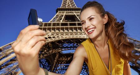 Touristy, 의심의 여지가 있지만, 아직 재미. 파리, 프랑스 에펠 탑에 대 한 디지털 카메라와 셀 차를 복용하는 젊은여자가 미소 스톡 콘텐츠