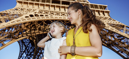Touristy, without doubt, but yet so fun. happy mother and daughter tourists using a cell phone in the front of Eiffel tower in Paris, France
