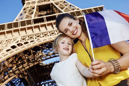 Touristy, 의심의 여지가 있지만, 아직 재미. 파리, 프랑스에서 에펠 타워의 앞에 플래그를 게재하는 엄마와 아기를 관광객 웃 고