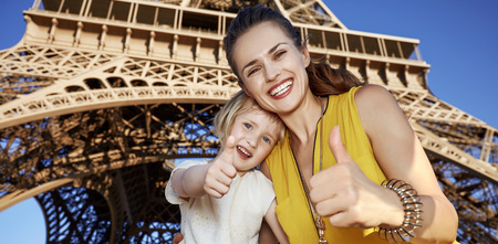 Touristy, without doubt, but yet so fun. Portrait of happy mother and daughter travellers showing thumbs up against Eiffel tower in Paris, France