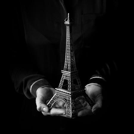 Black Mania. mains féminines isolées sur fond noir montrant la tour eiffel Banque d'images - 99979042