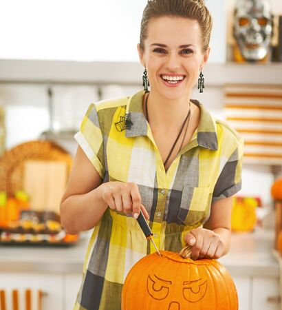 Frightful Treats on the way. happy young woman in the Halloween decorated kitchen carving a big orange pumpkin Jack-O-Lantern