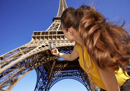 Touristy, 의심의 여지가 있지만, 아직 재미. 프랑스 파리에서에서 에펠 타워에 [NULL]에 대해 디지털 카메라와 사진을 복용하는 젊은 여자 뒤에서