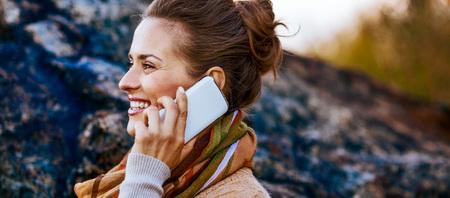 秋の夜に屋外で携帯電話を話して幸せな若い女