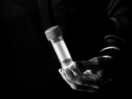 Black Mania. woman hand isolated on black showing sample jar Stock Photo