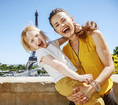 Having fun time near the world famous landmark in Paris. Portrait of cheerful mother and child hugging in Paris, France