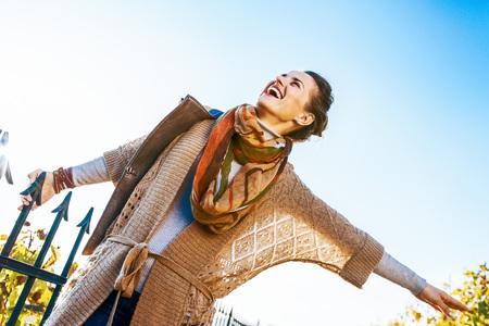행복한 젊은 여자가 가을 야외에서 시간을 보내고