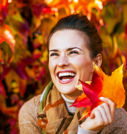 Portrait of smiling young woman with autumn leafs in front of foliage