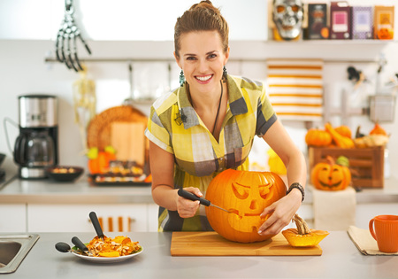 Frightful Treats on the way. Portrait of smiling modern housewife in the Halloween decorated kitchen carving a big orange pumpkin Jack-O-Lantern