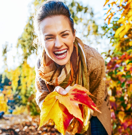Laughing young woman holding colorful autumn leafs in city park photo