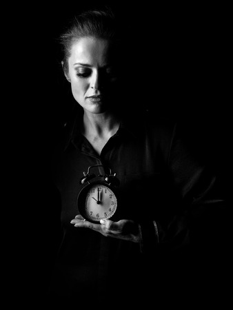 ?oming out into the light. Portrait of woman in the dark dress isolated on black background showing alarm clock photo