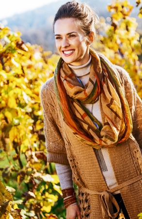 Happy young woman in autumn vineyard photo