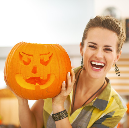 Frightful Treats on the way. Portrait of happy young housewife in the Halloween decorated kitchen showing a big orange pumpkin Jack-O-Lantern
