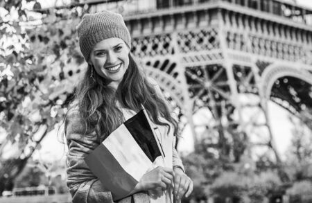 Autumn getaways in Paris. smiling young elegant woman on embankment in Paris, France with flag