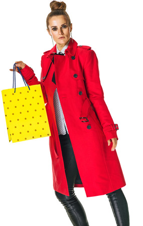 Keep the autumn bright. modern woman in red coat isolated on white background showing yellow shopping bag Stock Photo