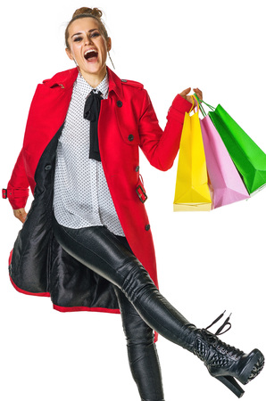 Keep the autumn bright. cheerful modern woman in red coat isolated on white with shopping bags