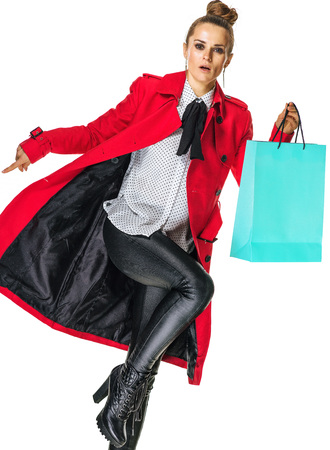 Keep the autumn bright. Full length portrait of stylish woman in red coat isolated on white background with shopping bag