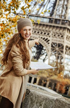 Autumn getaways in Paris. Portrait of smiling young tourist woman on embankment near Eiffel tower in Paris, France holding map and pointing