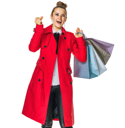 Keep the autumn bright. Full length portrait of smiling stylish woman in red coat isolated on white with shopping bags snapping fingers