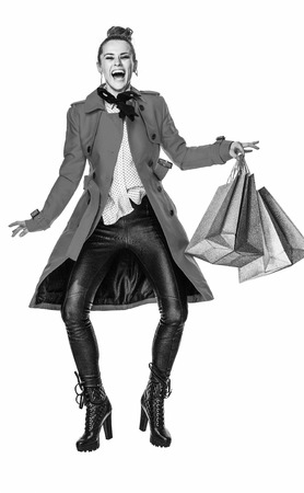 Keep the autumn bright. Full length portrait of happy modern woman in red coat isolated on white background jumping with shopping bags