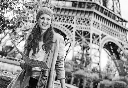 Autumn getaways in Paris. smiling young tourist woman on embankment in Paris, France  holding map and looking into the distance