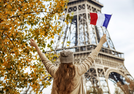 Autumn getaways in Paris. Seen from behind young elegant woman on embankment in Paris, France rising flag Stock Photo