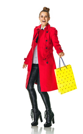 Keep the autumn bright. Full length portrait of smiling trendy woman in red coat isolated on white background with yellow shopping bag Stock Photo