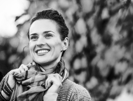 Portrait of happy young woman in autumn outdoors in evening photo