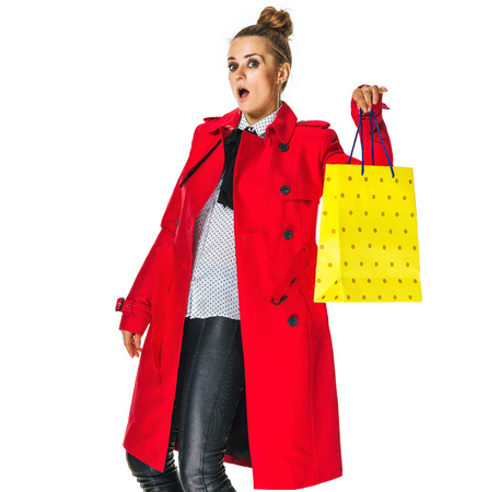 Keep the autumn bright. Full length portrait of surprised modern woman in red coat isolated on white background showing yellow shopping bag