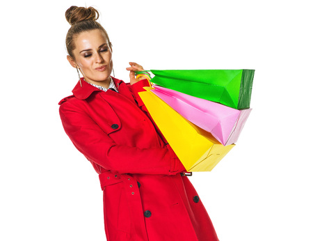 Keep the autumn bright. happy modern woman in red coat isolated on white background with shopping bags