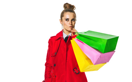 Keep the autumn bright. Full length portrait of pensive young woman in red coat isolated on white background with shopping bags Stock Photo