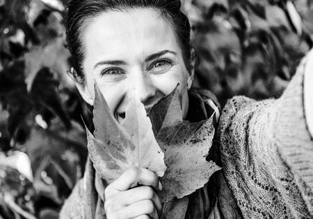 紅葉の前に selfie しながら葉の後ろに隠れて幸せな若い女