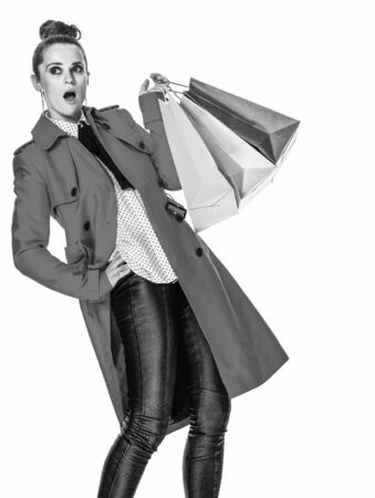Keep the autumn bright. surprised trendy woman in red coat isolated on white background with shopping bags looking on copy space Stock Photo