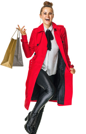 Keep the autumn bright. Full length portrait of happy trendy woman in red coat isolated on white with shopping bags Stock Photo