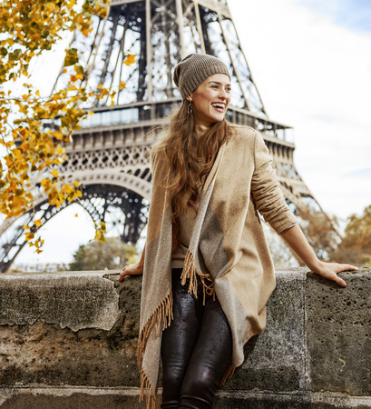 Autumn getaways in Paris. smiling young elegant woman on embankment in Paris, France exploring attractions