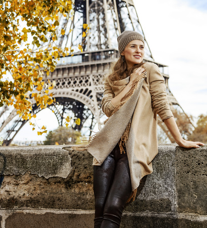 Autumn getaways in Paris. relaxed young elegant woman on embankment in Paris, France looking aside