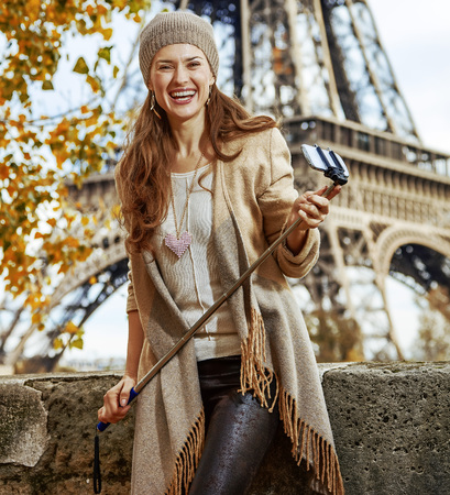 Autumn getaways in Paris. Portrait of happy young tourist woman on embankment near Eiffel tower in Paris, France with selfie stick photo