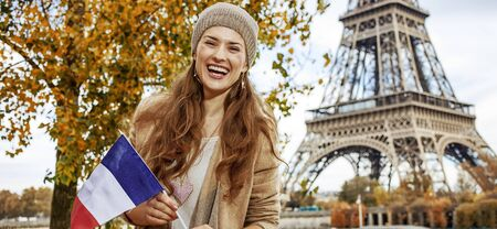 Autumn getaways in Paris. Portrait of smiling young elegant woman on embankment near Eiffel tower in Paris, France showing flag photo