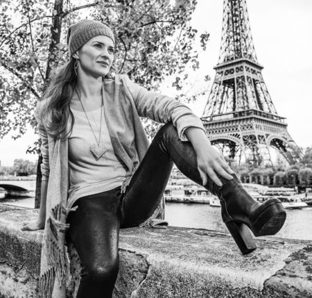 Autumn getaways in Paris. young elegant woman on embankment in Paris, France looking into the distance while sitting on parapet Stok Fotoğraf