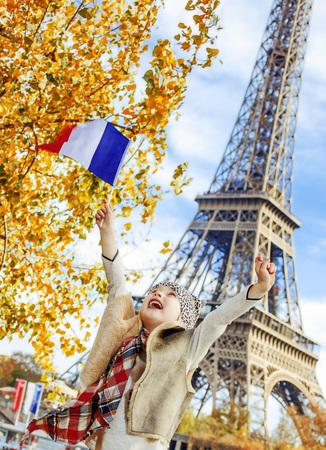 Spaßzeit nahe dem weltberühmten Markstein in Paris haben. fröhliches elegantes Kind auf Damm in der Nähe von Eiffelturm in Paris, Frankreich Jubel und steigende Flagge beim Sitzen auf dem Geländer Standard-Bild - 84584961