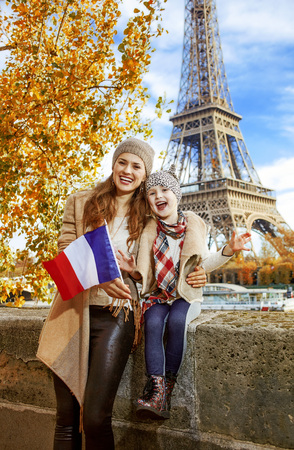 Autumn getaways in Paris with family. Portrait of happy mother and child travellers on embankment in Paris, France showing flag