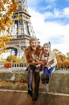 Autumn getaways in Paris with family. Portrait of smiling mother and child tourists on embankment in Paris, France having fun time Banco de Imagens