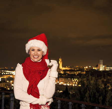 michelangelo: Trip full of inspiration at Christmas time in Florence. smiling young woman in Christmas hat in the front of panoramic view of Florence