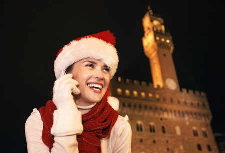 Trip full of inspiration at Christmas time in Florence. Portrait of smiling young tourist woman in Christmas hat against Palazzo Vecchio in Florence, Italy talking on a cell phone
