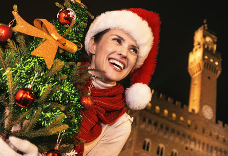 Trip full of inspiration at Christmas time in Florence. Portrait of smiling modern woman in Christmas hat in the front of Palazzo Vecchio in Florence, Italy with Christmas tree looking into the distance