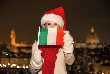 Trip full of inspiration at Christmas time in Florence. happy young woman in Christmas hat in Florence, Italy showing flag